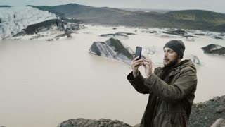 Young handsome man hiking, taking photo of Vatnajokull ice lagoon with glaciers in Iceland on smartphone.