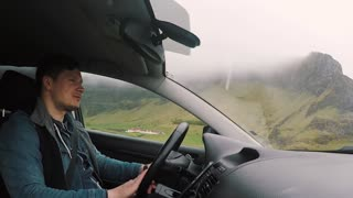 Young handsome man riding the car through the beautiful road in the mountains. Male driver talking with people, friends.