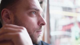 Young handsome man sitting alone at the cafe, waiting and looking out the window. Hands in front of face. Close-up, 4K