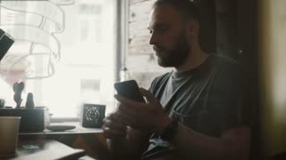 Young handsome man sitting in cafe, drinking coffee and holding the smartphone, using wireless technology.
