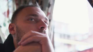 Young handsome man sitting in cafe near window and look into distance. Holding hands in front of face. Close-up, 4K