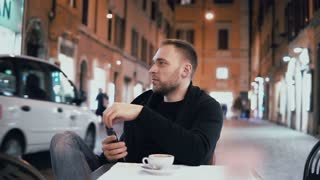 Young handsome man sitting outside in the city cafe and holding smartphone. Male drinking coffee in the evening.
