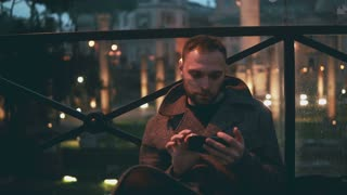 Young handsome man using smartphone, evening city on a background. Man browse the Internet with touchscreen technology.