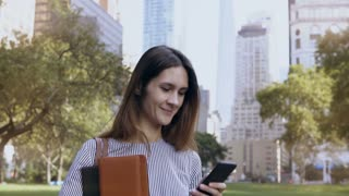Young happy businesswoman standing in financial district of New York, USA and using the smartphone as mobile office.