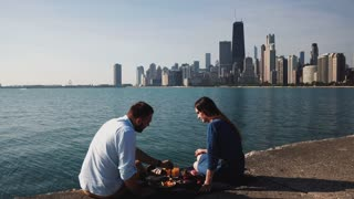 Young happy couple enjoying romantic date on the shore of Michigan lake with panoramic view of Chicago, America.