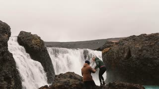 Young happy couple hiking together to see a powerful waterfall in Iceland. Man and woman raising hands up.