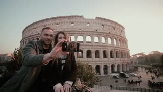 Young happy couple taking a selfie photo on smartphone. Attractive man and woman near the Colosseum in Rome, Italy.