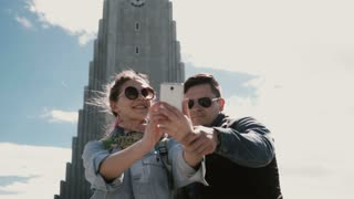 Young happy couple taking the selfie photo on smartphone near the Hallgrimskirkja church in Reykjavik, Iceland.