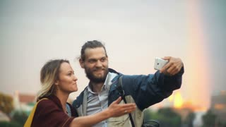 Young happy couple taking the selfie photos with rainbow on background. Smiling man and woman use smartphone.