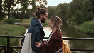 Young happy couple walking in the park with river on sunset. Beautiful man and woman hug, talk on the bridge.