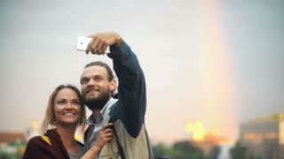 Young happy couple walking on sunset and taking the selfie photos. Smiling man and woman use smartphone.