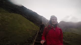 Young happy woman holding selfie stick with gopro and going down from the stairs. Couple traveling in mountains. Slow mo
