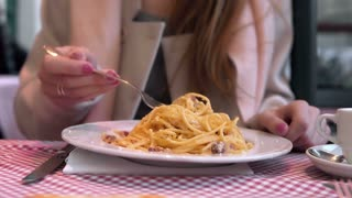 Young happy woman sitting at the table in cafe and enjoying the meal. Hungry woman eating tasty pasta.