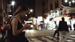 Young happy woman standing in crowded downtown, near the traffic road in New York, America and using the smartphone.