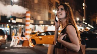 Young happy woman standing near the traffic road in New York, America downtown and talking on mobile phone.