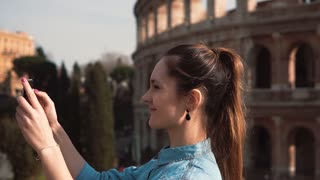 Young happy woman takes selfie on her smartphone in Rome, Italy, enjoying the trip, watching the pictures. Slow motion.