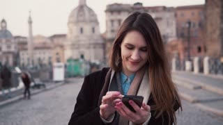 Young happy woman walking in city and using smartphone. Girl browse the Internet, spending vacation in Rome, Italy.