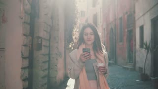 Young happy woman walking in city centre at morning, using smartphone. Girl surfing the Internet, texting with someone.