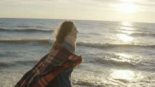 Young happy woman walking on beach on sunset. Beautiful female goes on shore of the sea with plaid in stretched arms.