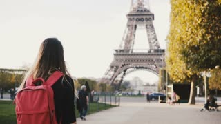 Young happy woman with backpack walking alone near the Eiffel tower and mars champs in Paris, France.