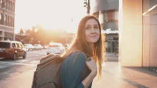 Young happy woman with backpack walking in downtown alone. Beautiful female turns and smiling at camera.