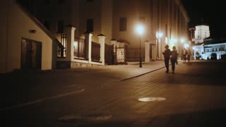 Young hipster couple hugging, walking in the city centre in the evening. Man and woman having fun together.