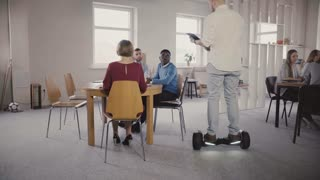 Young male boss using hoverboard to come and talk to colleagues. Confident leader uses technology in modern office 4K.