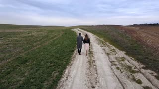 Young man and woman goes through the countryside. Aerial view, drone flying over a couple who walks on field. Back view.