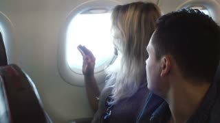Young man and woman sitting near the window and looking on the view outside. Couple traveling by plane together.