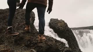 Young man and woman standing on a hill after hiking and looking on a powerful waterfall in Iceland, famous sight.