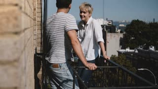 Young man and woman standing together, enjoying talking and flirting at a small sunny balcony with lovely New York view.
