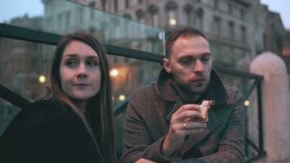 Young man and woman, two friends sitting on the bridge in evening and eating sandwiches. Couple have a break.