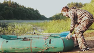 Young man in camouflage uniform puts rubber boat from the coast on the water. Male preparing to fishing.