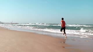 Young man runs along seashore. Summer beach. Freedom concept. European male enjoying holiday vacations. Mediterranean 4K