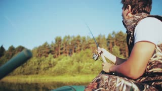 Young man sits in the boat at forest lake and throws a rod. Attractive male catching fish with rod with spinning reel.