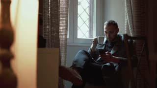 Young man sitting in armchair in living room and using smartphone. Attractive male browse the Internet, drinks coffee.