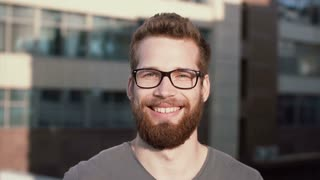 Young man smiling and looking at camera. Portrait of happy handsome young guy in urban street. Male touches the glasses.