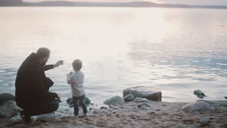 Young man squatting on a shore and talking with little boy, than stand up. Father and son spending time together.