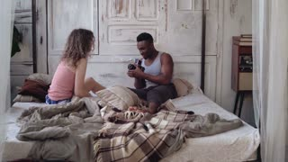 Young man taking photo of woman in pajamas on the moving-film camera. Multiracial couple sitting on the bed in morning.