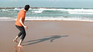 Young man walks on summer sea beach, throws stone. Freedom and retreat concept. Thinking about life. Big foam waves. 4K