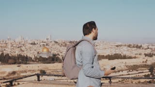 Young man with backpack at Jerusalem scenery. Thoughtful happy European male tourist walks away. Israel. Slow motion.