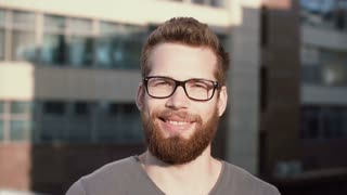 Young man with beard and glasses standing in street and looking at camera. Guy seriously looks and then starts to smile.