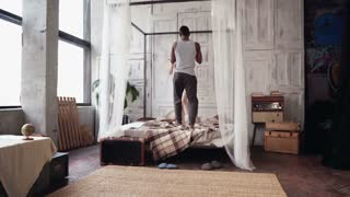 Young multiethnic couple in pajamas dancing, jumping on the bed. African boy and europen woman have fun in the morning.