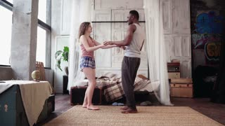Young multiracial couple dancing in the morning in light apartment. African man and european woman have fun together.