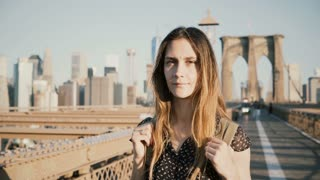 Young positive female Caucasian tourist with backpack looking at camera, smiling at sunny Brooklyn Bridge, New York 4K.