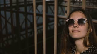 Young positive female European tourist in stylish sunglasses smiling, looking up enjoying the view at Brooklyn Bridge 4K