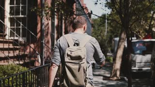 Young relaxed Caucasian male tourist with backpack walking along sunny summer city street in New York drinking coffee.