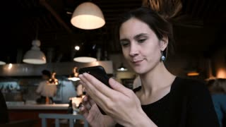 Young smiling woman sitting in cafe and using the smartphone. Attractive female chatting in social networks with friends
