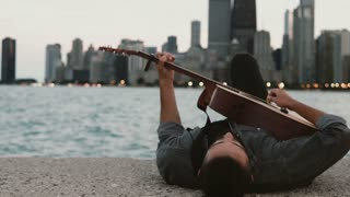 Young stylish man lying on the shore of the Michigan lake in Chicago, America and playing the acoustic guitar.