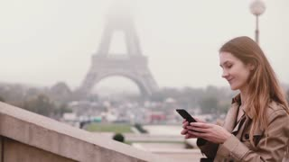Young stylish woman going upstairs and using the smartphone near the Eiffel tower in Paris, France. Slow motion.